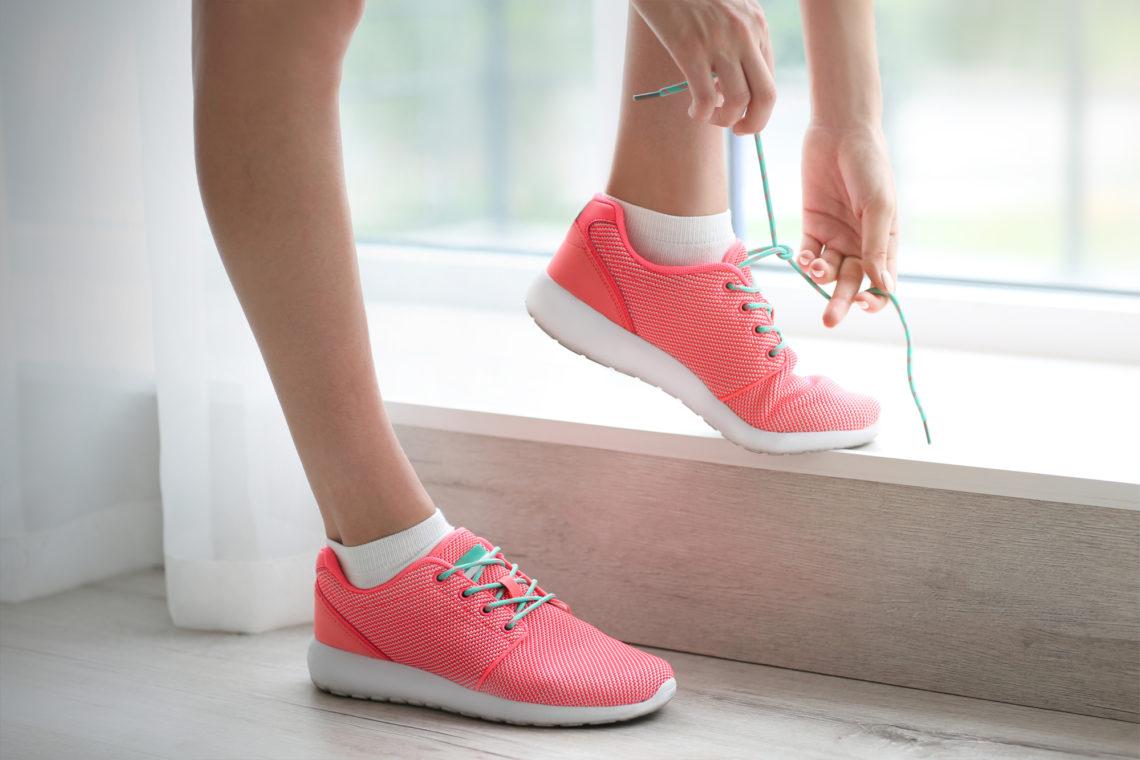 Bilden visar ett par rosa skor med skosnören som en kvinna knyter framför ett fönster