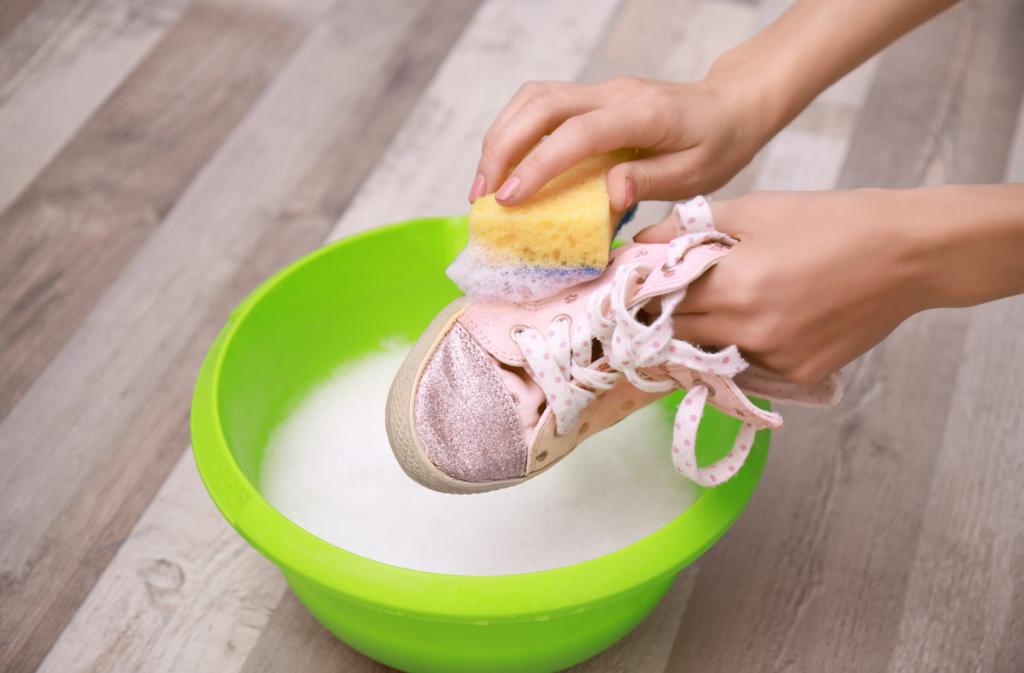Hink med tvålvatten, person som skrubbar en sko ovanför med en svamp